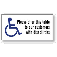 Package of 6 Transparent Labels for Restaurant Tables- with Wheelchair Symbol (ISA) and text reading: Please offer this table to our customers with disabilities- 4x2
